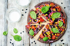 Les haricots noirs couvrent la pizza d'une croûte avec du maïs, épinards, tomates, haricot noir photographie stock libre de droits
