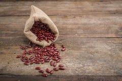 Les haricots rouges secs en toile de jute renvoient, les haricots rouges dans le sac de toile de jute Photo libre de droits
