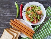 Les haricots verts de salade, tomate, plat gastronome de nutrition ont fait frire des saucisses sur un fond en bois, poivron roug Photographie stock