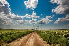 Les hauts piliers de l'électricité sur la route de campagne sous le ciel bleu opacifie photographie stock