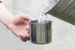 Les helds de main de Man's une tasse en acier et une eau de puits verse d'un seau image stock
