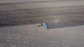 Les herses de tracteur le sol sur le champ pour l'ensemencement images stock