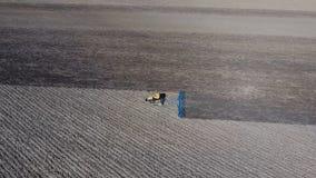 Les herses de tracteur le sol sur le champ pour l'ensemencement photos stock
