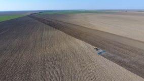 Les herses de tracteur le sol sur le champ pour l'ensemencement image stock