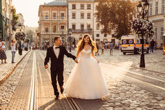 Les heureux couples de mariage se tiennent des mains tout en courant Photo stock