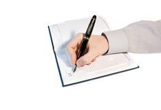 Les hommes écrivent en agenda Photographie stock