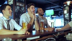 Les hommes évente le football de observation sur la bière de TV et de boissons banque de vidéos
