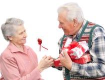 Les hommes aînés donnent des femmes d'aîné de cadeaux Photos stock