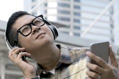 Les hommes asiatiques ont mis les verres noirs de cadre, écoutant la musique l'en public images libres de droits