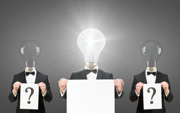 Les hommes avec des ampoules au lieu des têtes gardent des copyspaces Photo stock