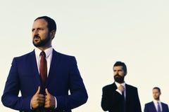 Les hommes avec la barbe et les visages sérieux regardent de côté Veste de contacts d'hommes d'affaires Les directeurs portent le photos libres de droits