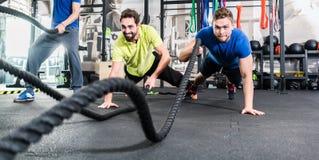 Les hommes avec la bataille rope dans le gymnase fonctionnel de forme physique de formation Photos libres de droits