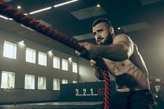Les hommes avec la corde de bataille luttent des cordes s'exercent dans le gymnase de forme physique photographie stock