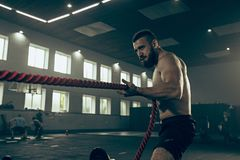 Les hommes avec la corde de bataille luttent des cordes s'exercent dans le gymnase de forme physique images stock