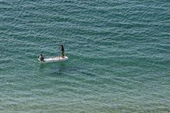 Les hommes barbotent un bateau à travers le port à l'Alexandrie en Egypte Photo stock