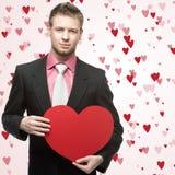 Les hommes beaux tiennent le grand coeur rouge Images stock