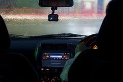 Les hommes conduisent la voiture le temps pluvieux la nuit photographie stock libre de droits