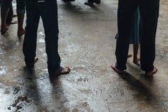 Les hommes dénudés de pied marchent autour de l'entrée élevée de cavernes de Batu près de Kuala Lumpur, Malaisie Photographie stock libre de droits