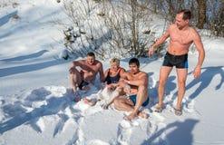 Les hommes déshabillés et une femme s'étendent sur la neige pelucheuse blanche comme neige, au Photographie stock libre de droits