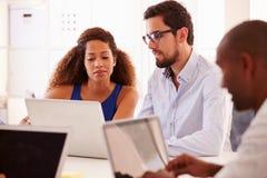 Les hommes d'affaires à l'aide de l'ordinateur portable dans le bureau de créent des affaires image stock