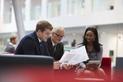 Les hommes d'affaires discutent le document dans le lobby du bureau moderne Images stock