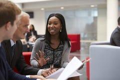Les hommes d'affaires discutent le document dans le lobby du bureau moderne image stock