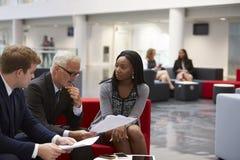 Les hommes d'affaires discutent le document dans le lobby du bureau moderne Photos libres de droits