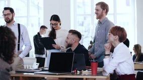 Les hommes d'affaires divers de sourire heureux écoutent le principal entretien de haut-parleur pendant la conférence moderne de  clips vidéos