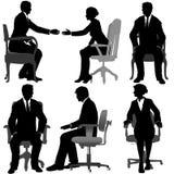 Les hommes d'affaires et les femmes d'affaires s'asseyent dans des présidences de bureau Image libre de droits