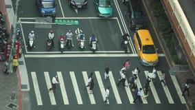 Les hommes d'affaires et les touristes asiatiques aériens marchent à travers la rue à Taïpeh banque de vidéos