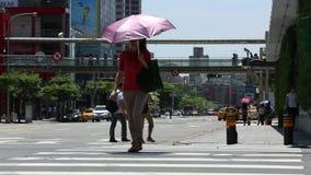 Les hommes d'affaires et les touristes asiatiques marchent à travers la rue dans la ville de Taïpeh clips vidéos