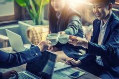 Les hommes d'affaires font tinter le café chaud au succès Photographie stock libre de droits