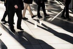 Les hommes d'affaires marchant rapidement sur le trottoir de ville silhouetté à la lumière du soleil lumineuse, un homme tient le Photographie stock