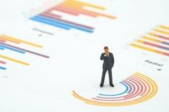 Les hommes d'affaires miniatures de personnes analysent la position sur des WI de graphique de cercle photographie stock libre de droits