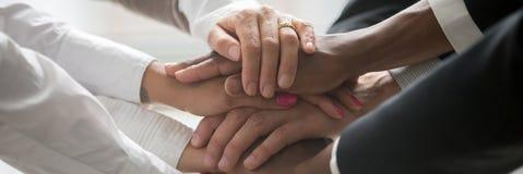 Les hommes d'affaires multinationaux empilent leur symbole de mains ensemble de l'unité photo stock