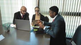 Les hommes d'affaires multiraciaux à la table dans la salle de conférences discutent de nouveaux plans et tâches dans le mouvemen clips vidéos