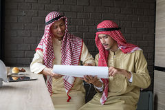 Les hommes d'affaires musulmans ont la réunion en café photographie stock