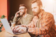 Les hommes d'affaires occupés et sérieux woking en café L'un d'entre eux travaille sur l'ordinateur tandis qu'un autre parle sur photographie stock