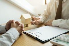 Les hommes d'affaires présentent le contrat des prix sur le commerce - louez une maison à photographie stock