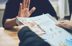 Les hommes d'affaires refusent de devenir payés avec les avantages qui le font Photographie stock libre de droits