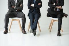 Les hommes d'affaires s'asseyant sur des chaises d'isolement sur le blanc, hommes d'affaires groupent le concept Image stock