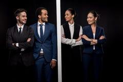 Les hommes d'affaires sûrs ont séparé par le mur avec les femmes d'affaires de sourire Photos stock