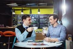 Les hommes d'affaires travaillent en café Image stock