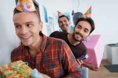 Les hommes dans des chapeaux d'anniversaire préparent une fête d'anniversaire de surprise Ils préparent pour rencontrer la fille  Photo stock