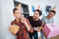 Les hommes dans des chapeaux d'anniversaire préparent une fête d'anniversaire de surprise Ils préparent pour rencontrer la fille  Photo libre de droits