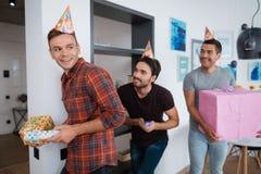 Les hommes dans des chapeaux d'anniversaire préparent une fête d'anniversaire de surprise Ils préparent pour rencontrer la fille  Photos stock