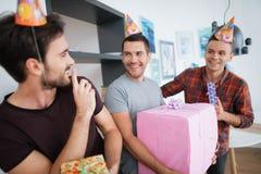 Les hommes dans des chapeaux d'anniversaire préparent une fête d'anniversaire de surprise Ils préparent pour rencontrer la fille  Image libre de droits