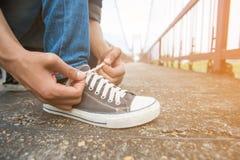 Les hommes dans des jeans attachent ses chaussures Image stock