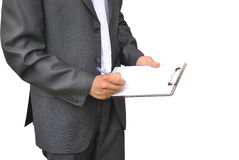 Les hommes dans le costume foncé écrit sur le presse-papiers avec le stylo Photographie stock