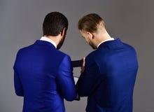 Les hommes dans le costume ou les hommes d'affaires tiennent le document sur papier Image stock